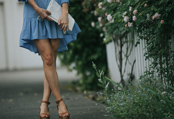 blue dress with white clutch