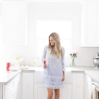 Erika Altes from Whiskey and Lace in kitchen wearing purple lace dress.
