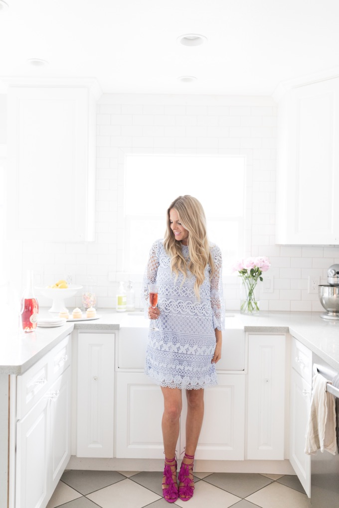 Erika Altes from Whiskey and Lace blog standing in kitchen wearing a purple lace dress