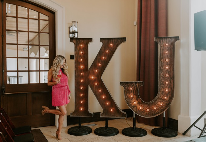 Kendall Jackson Wines Meet and Greet by popular SoCal wine blog, Whiskey and Lace: image of a woman standing next to a letter K and J marquis sign.