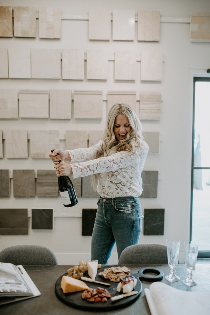 Ceramic Tile Center by popular SoCal life and style blog, Whiskey and Lace: image of a woman opening a bottle of wine at the Ceramic Tile Center.