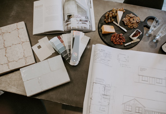 Ceramic Tile Center by popular SoCal life and style blog, Whiskey and Lace: image of tile samples, paint swatches, a house blue print, and a charcuterie board on a counter at the Ceramic Tile Center.