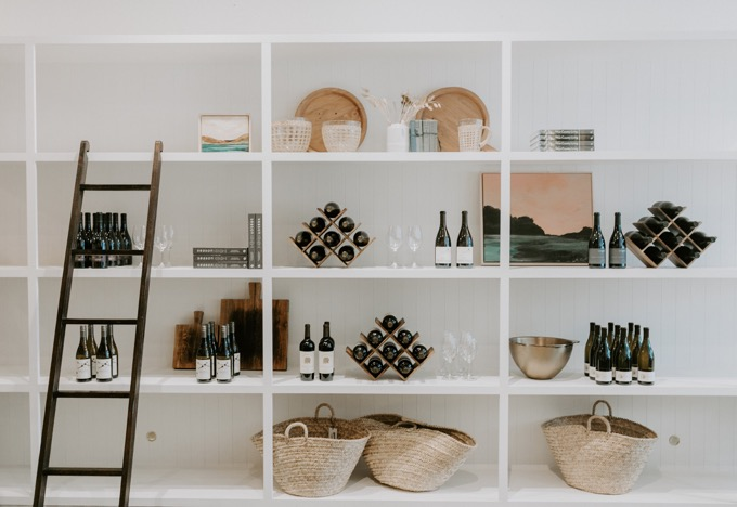 Whiskey & Lace Online Wine Club |Wine Club by popular Northern California lifestyle blog, Whiskey and Lace: image of a wine display on white wooden shelves next to woven baskets, art work, books, and wooden cutting boards.