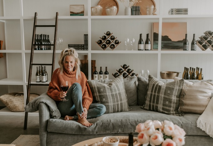 Whiskey & Lace Online Wine Club | Wine Club by popular Northern California lifestyle blog, Whiskey and Lace: image of a woman sitting on a grey couch and holding a glass of red wine.